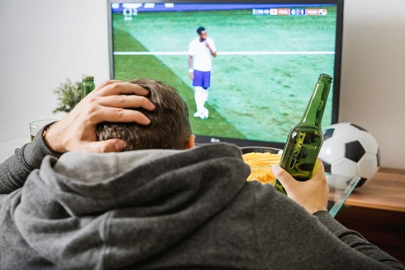 גבר צופה בטלוויזיה - פעילות גופנית משתלמת בין הסלון למטבח